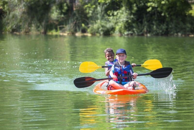 Dois rapazes pequenos diversos que kayaking abaixo de um rio bonito foto de stock