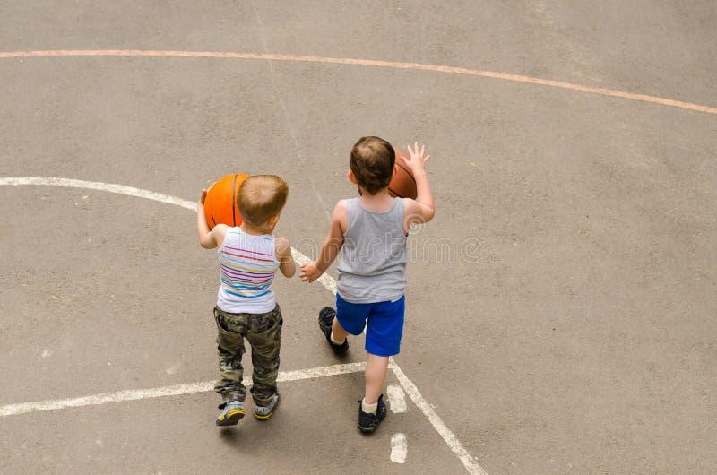 Dois rapazes pequenos que jogam em um campo de básquete fotos de stock royalty free