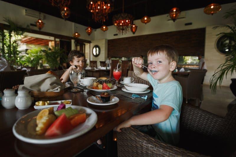 Dois rapazes pequenos têm o café da manhã em um café e sentam-se na tabela de jantar Na tabela de café da manhã há uma placa com  fotografia de stock royalty free