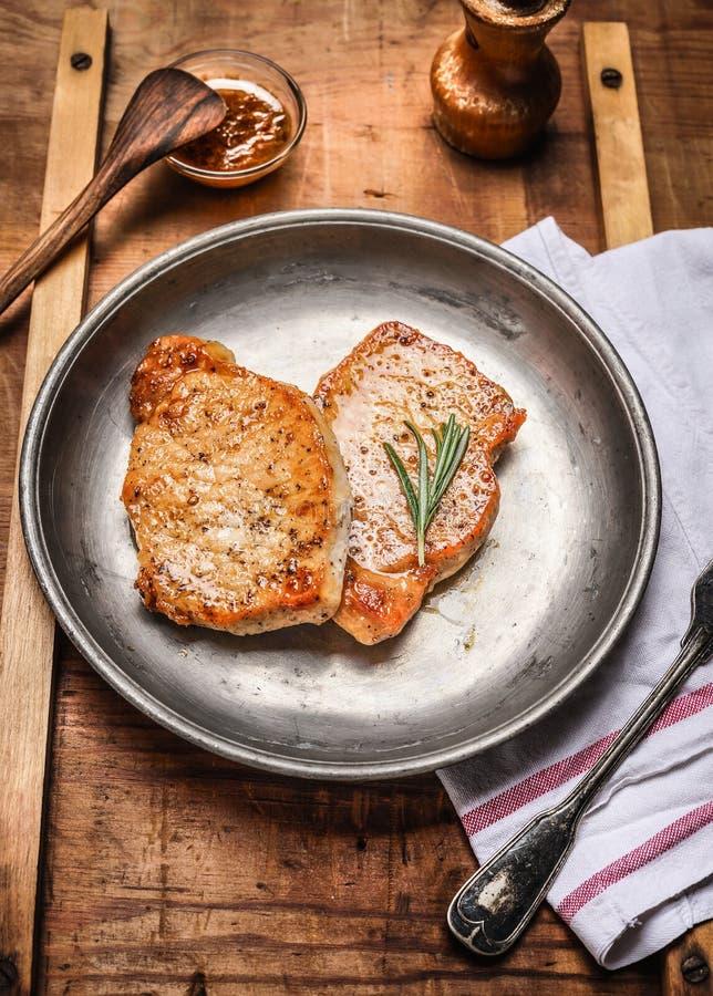 Dois roasted bifes da carne de porco na placa de metal rústica no fundo de madeira imagens de stock