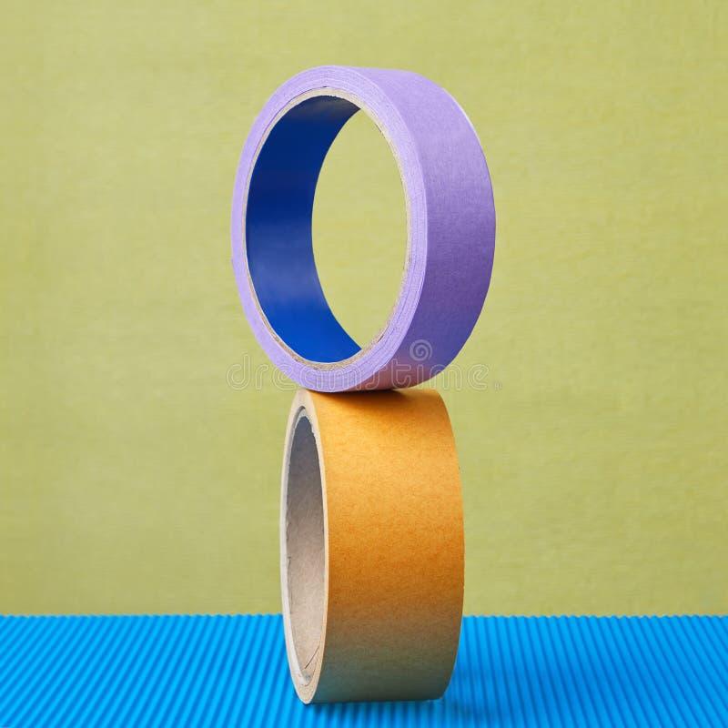 Dois rolos da fita pegajosa colorem o equilíbrio no fundo roxo foto de stock