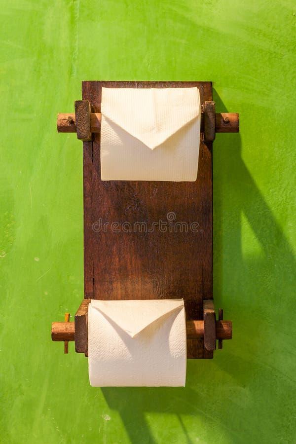 Dois rolos da suspensão de papéis higiênicos no suporte de madeira com t verde imagens de stock