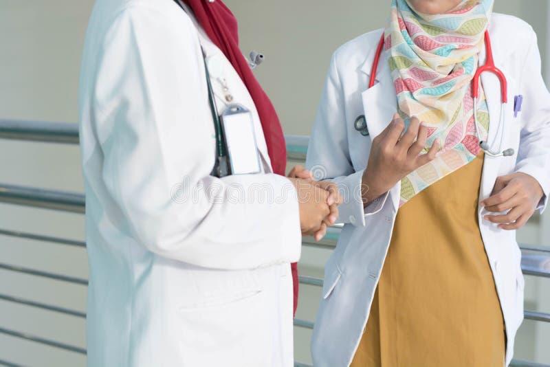 Dois sérios doutor asiático fêmea do hijab para discutir e estudando sobre o documento do paciente na sala de hospital fotografia de stock