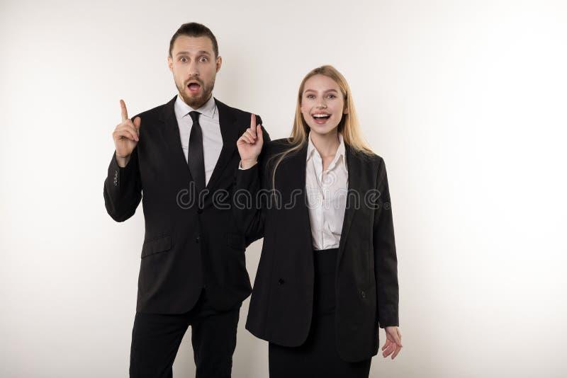 Dois sócios comerciais atrativos em ternos pretos vieram acima com uma ideia como melhorar seu negócio fotografia de stock