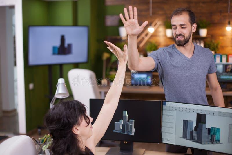 Dois sócios comerciais novos bem sucedidos dão um hi5 entre si imagem de stock royalty free