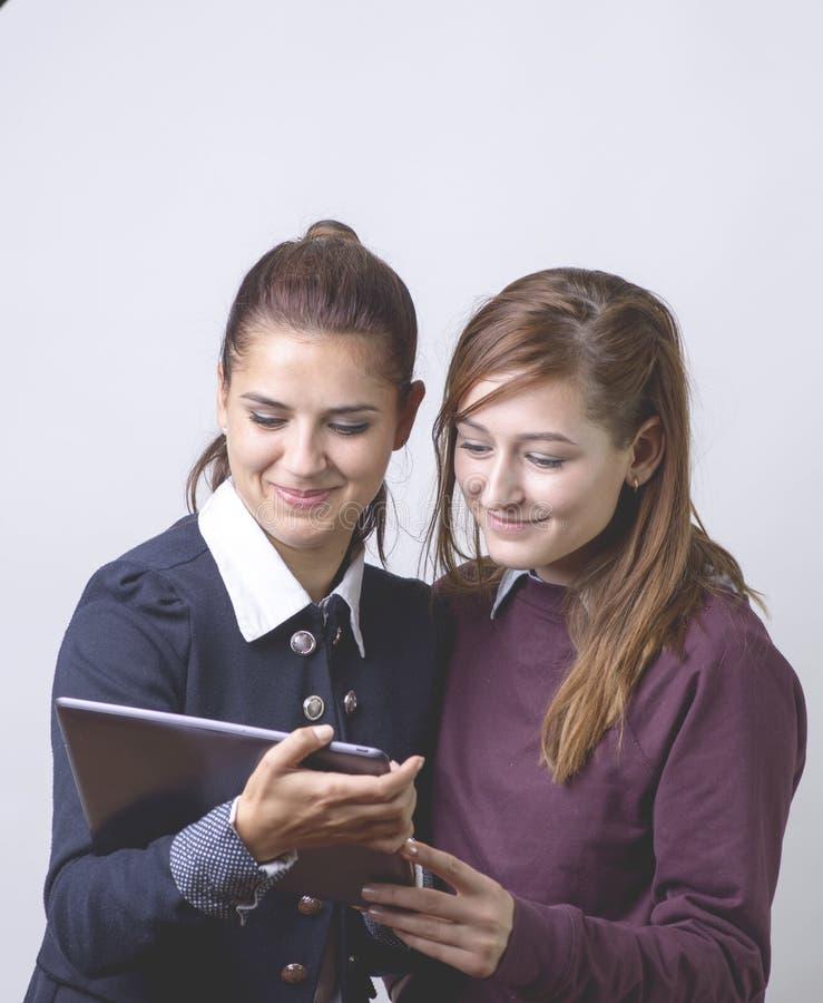 Dois sócios comerciais, olhando alguém vídeo engraçado na tabuleta e no sorriso Isolado imagem de stock royalty free