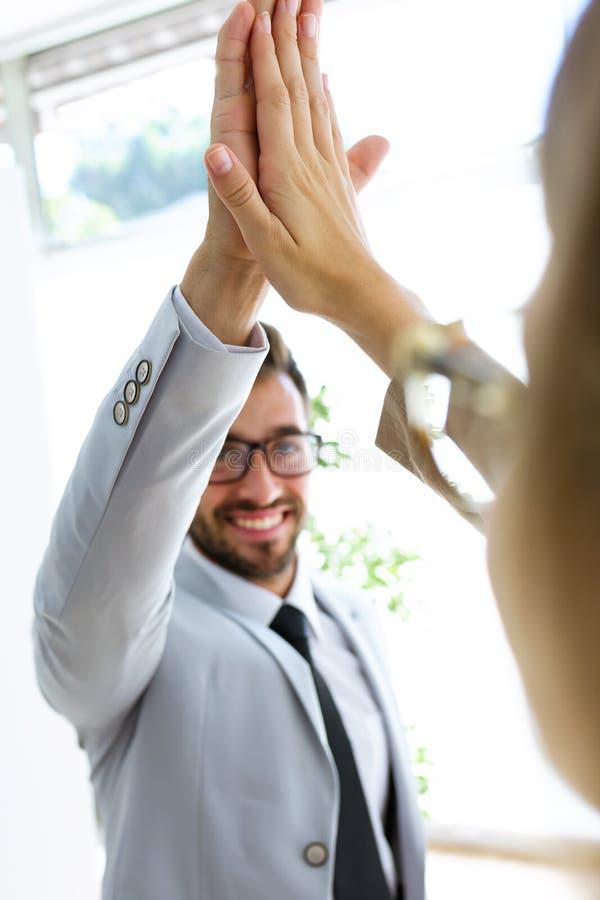 Dois satisfizeram os trabalhadores alegres felizes que têm o divertimento que sustenta seus assistentes em um corredor dos eles e foto de stock