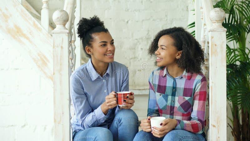 Dois sistres encaracolado afro-americanos das meninas que sentam-se em escadas têm o divertimento que ri e que conversa junto em  foto de stock