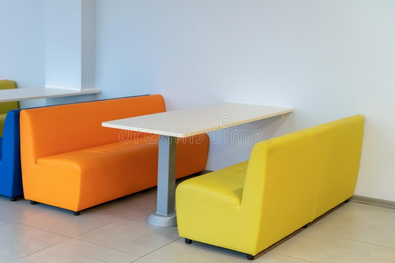 Dois sofás coloridos das poltronas com uma tabela na sala Benchs amarelos e alaranjados Design de interiores escola foto de stock royalty free