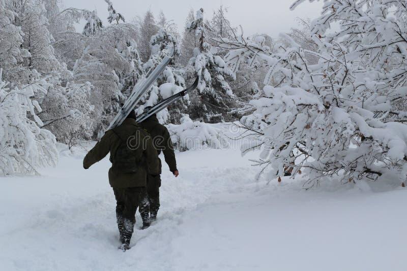 Dois soldados fazem sua maneira através da neve na floresta densa do inverno fotos de stock royalty free