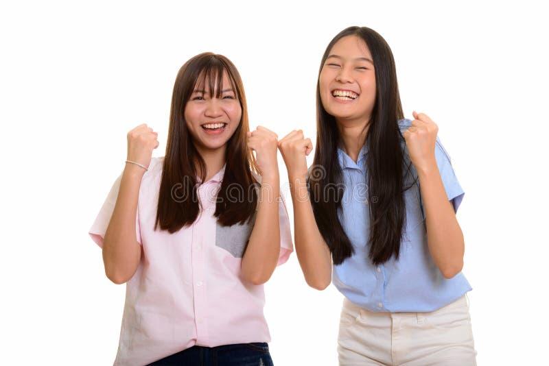 Dois sorrisos asiáticos felizes novos e ambos dos adolescentes que olham o mot fotografia de stock