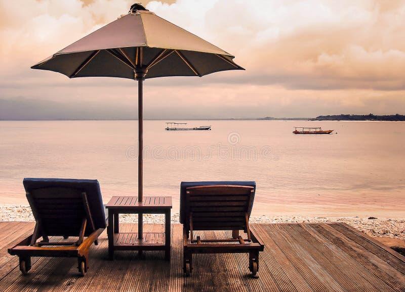 Dois sunbeds e guarda-chuvas que estão em uma plataforma de madeira na praia tropical no por do sol Conceito do resto calmo fotos de stock