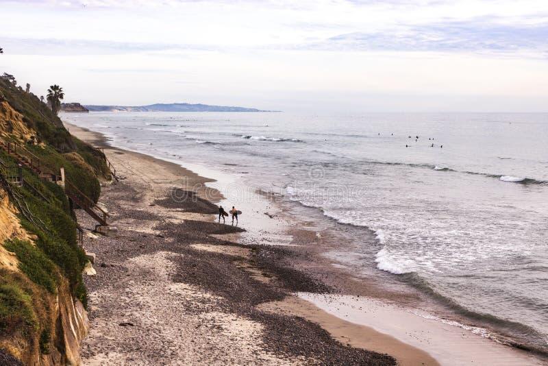 Dois surfistas andam acima de uma praia rochosa da linha costeira com rolamento da ressaca dentro e o montanhês verde imagem de stock royalty free
