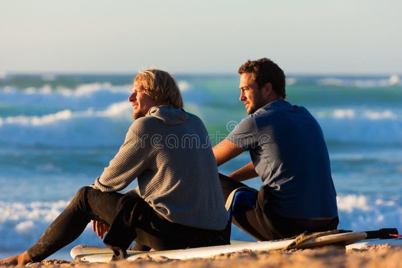 Dois surfistas que falam na praia fotografia de stock
