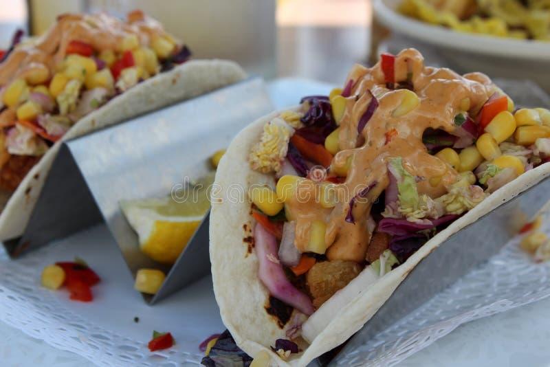 Dois tacos de peixes saborosos nas tortilhas macias cobertas com os vegetais e o molho fotografia de stock