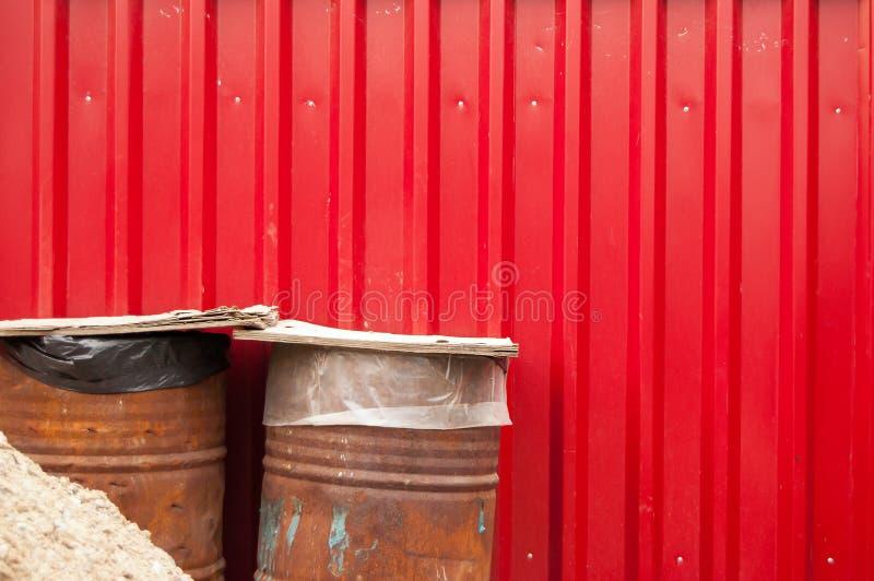 Dois tambores oxidados do metal cobertos com as placas contra a parede vermelha do metal imagens de stock
