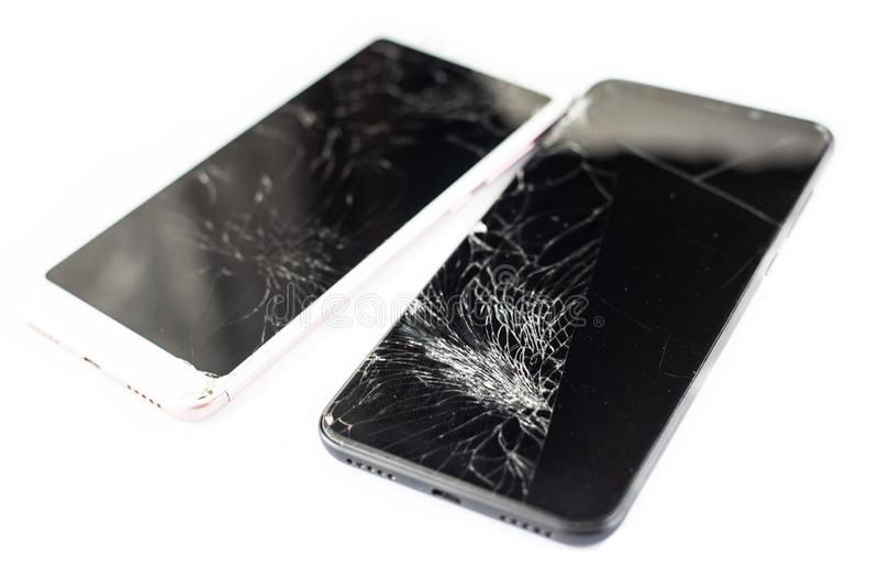 Dois telefones quebrados de branco e de preto em um fundo branco vidro rachado do écran sensível do isolado do tela táctil foto de stock