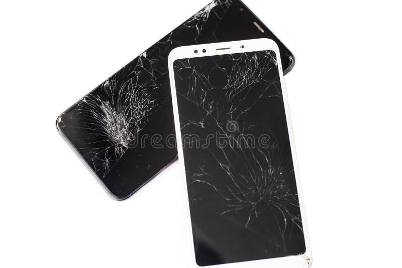 Dois telefones quebrados de branco e de preto em um fundo branco vidro rachado do écran sensível do isolado do tela táctil fotografia de stock royalty free