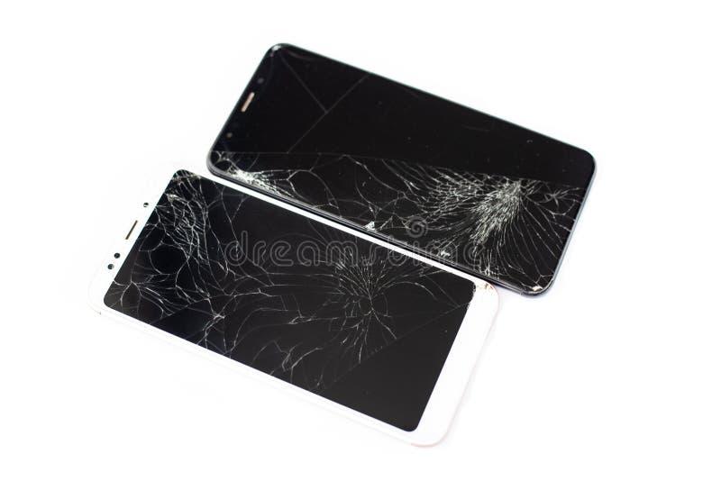 Dois telefones quebrados de branco e de preto em um fundo branco vidro rachado do écran sensível do isolado do tela táctil fotos de stock