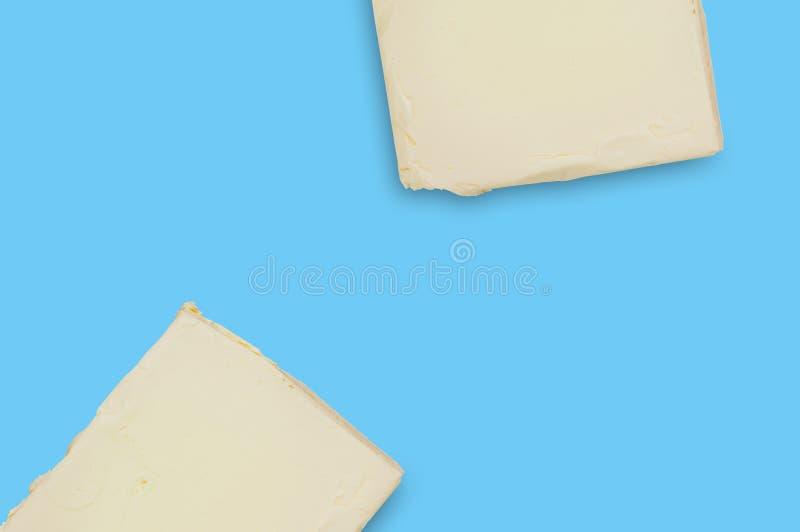 Dois tijolos da manteiga ou da margarina gorda na tabela azul na cozinha copie o espa?o para seu texto Vista superior fotografia de stock