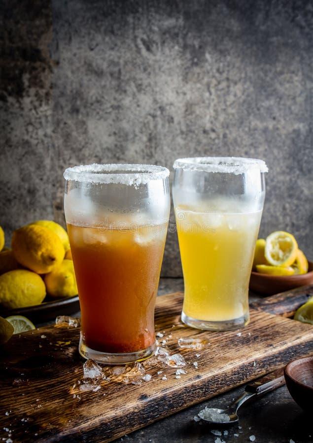 Dois tipos de cerveja latino-americano bebem Michelada com suco e sal de limão Michelada chileno e mexicano picante fotografia de stock