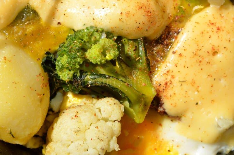 Dois tipos dos brócolis e da couve-flor são cobertos no ovo e no queijo derretido foto de stock royalty free