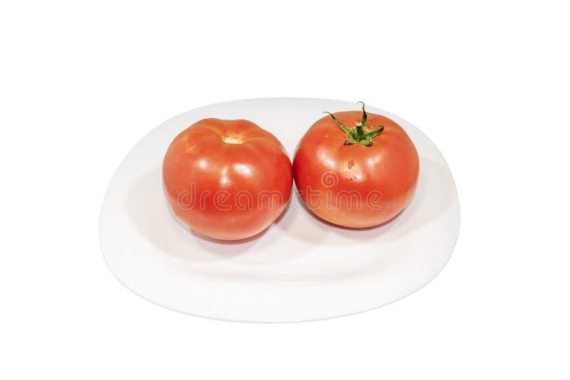 Dois tomates frescos no branco plat Trajeto de grampeamento foto de stock royalty free