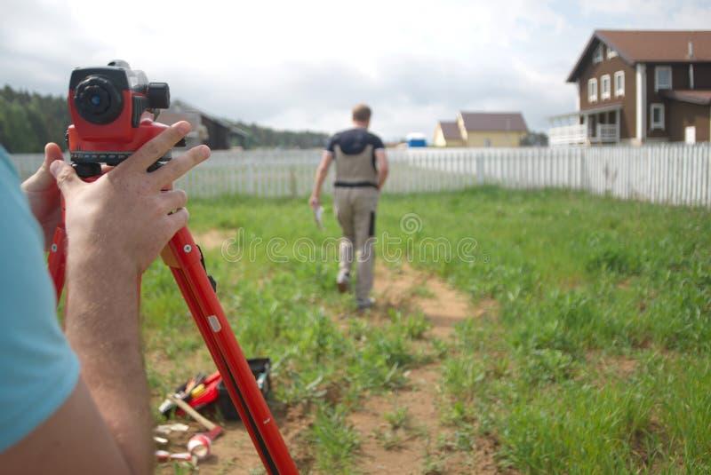 Dois topógrafos que medem a terra imagem de stock