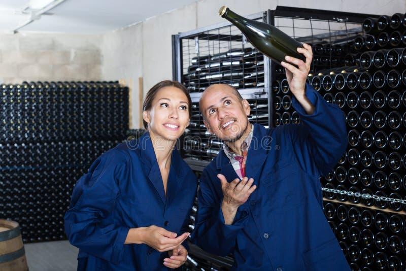 Dois trabalhadores adultos da adega que guardam a garrafa do vinho imagens de stock