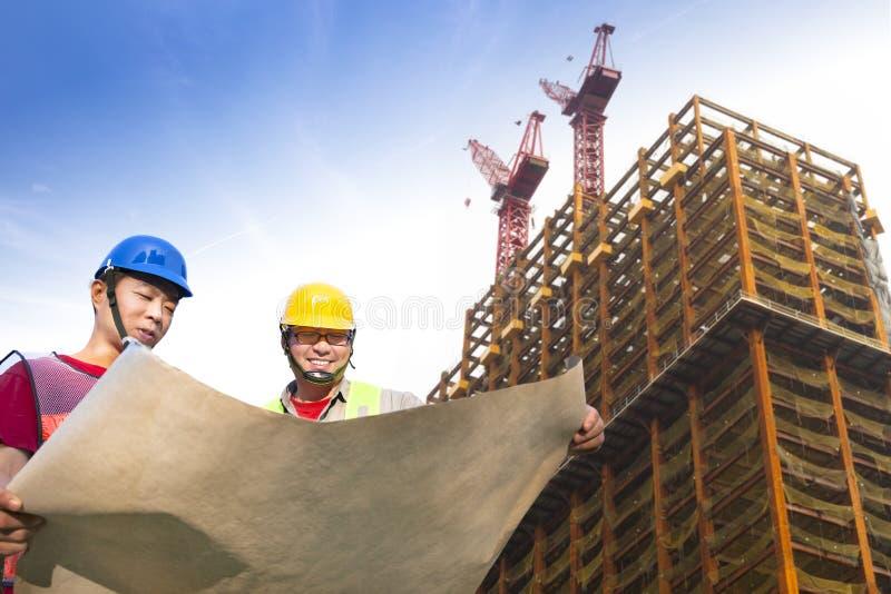 Dois trabalhadores da construção com construção imagem de stock