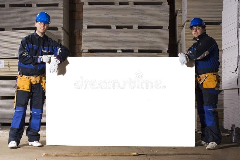 Dois trabalhadores da construção com tabela branca fotografia de stock royalty free