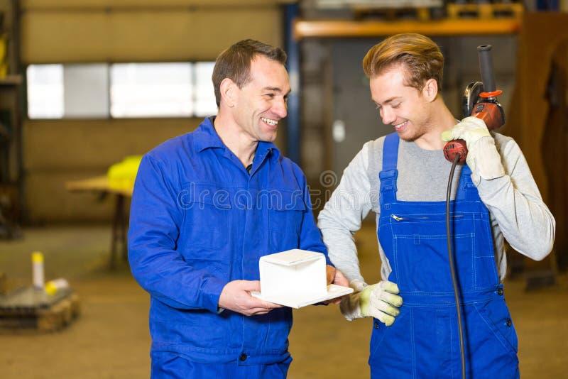 Dois trabalhadores da construção de aço que inspecionam partes do metal fotos de stock
