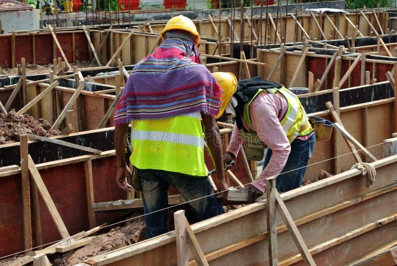 Dois trabalhadores da construção que fabricam o molde do feixe à terra fotografia de stock royalty free