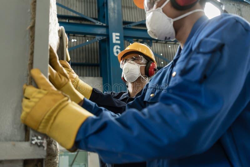 Dois trabalhadores de colarinho azul que vestem o equipamento de proteção imagem de stock