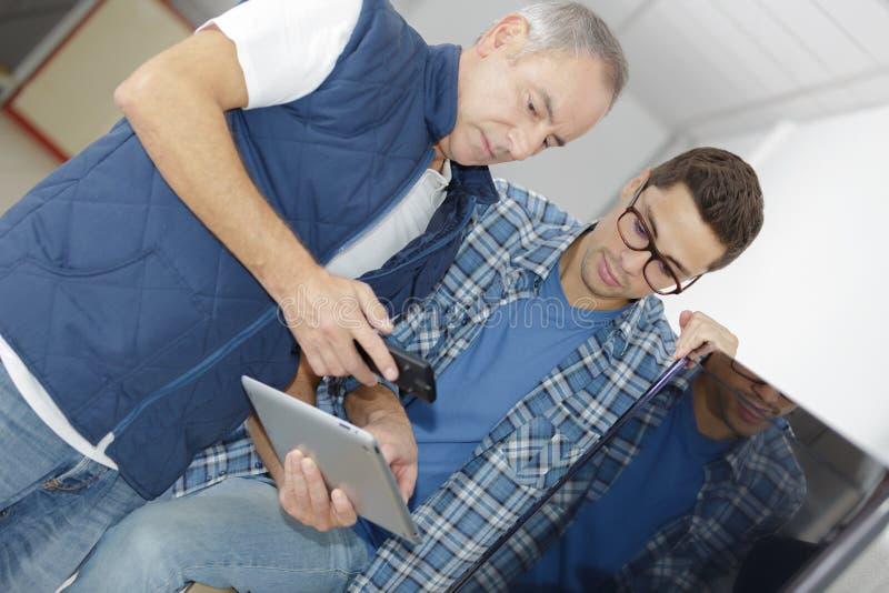 Dois trabalhadores dos gerentes no armazém com tablet pc imagens de stock