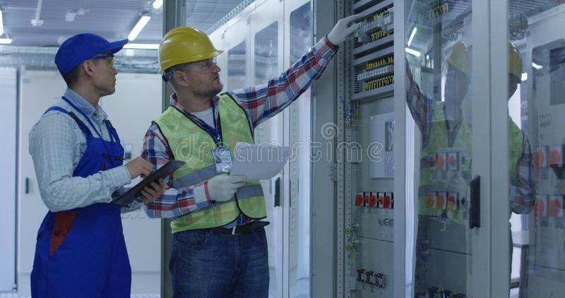 Dois trabalhadores elétricos que inspecionam o equipamento foto de stock royalty free