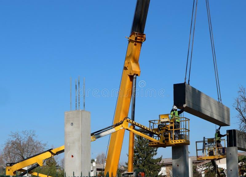 Dois trabalhadores em duas máquinas desbastadoras da cereja instalam uma laje de cimento da casa pré-fabricada, levantada por um  foto de stock royalty free