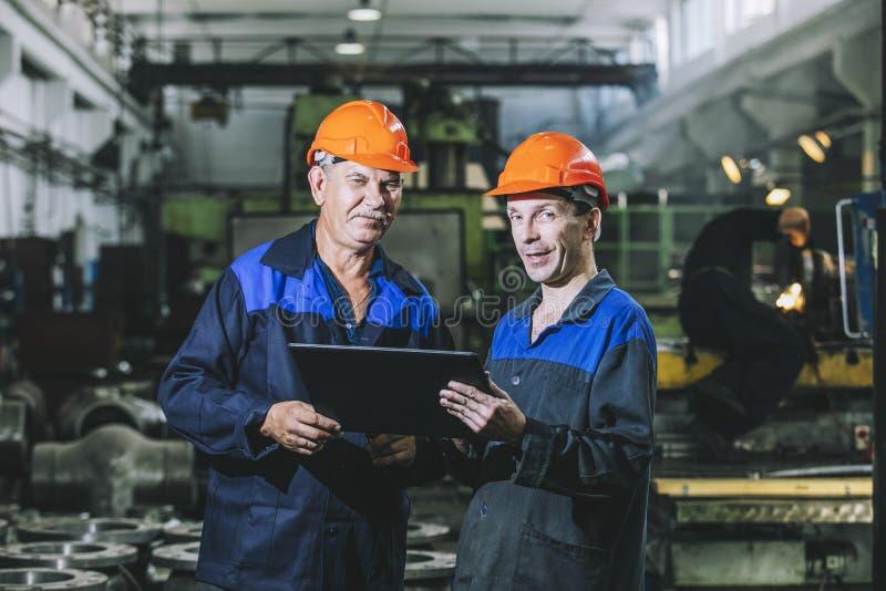 Dois trabalhadores em uma planta industrial com uma tabuleta à disposição, workin foto de stock