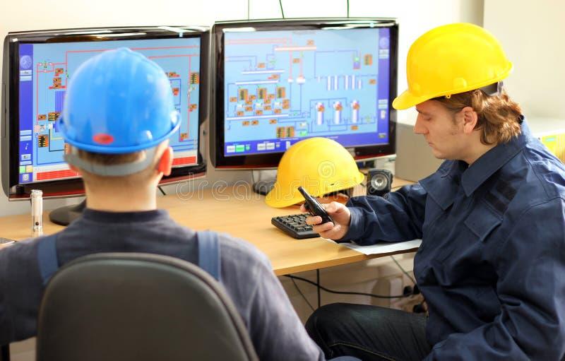 Dois trabalhadores em uma sala de comando