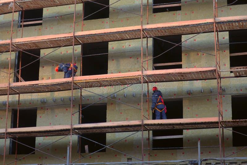 Dois trabalhadores instalam a isolação na parede da construção nova foto de stock