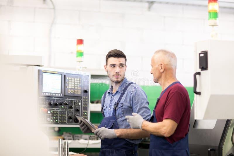 Dois trabalhadores na fábrica na máquina imagem de stock