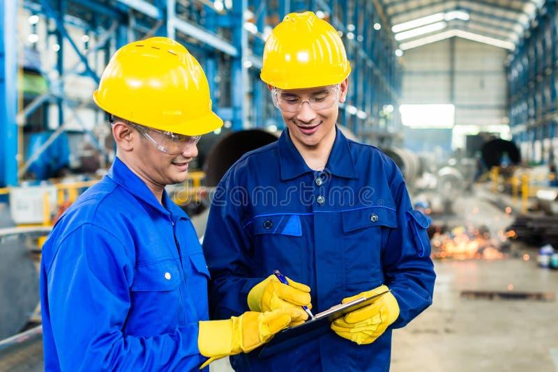 Dois trabalhadores na planta de produção como a equipe fotos de stock