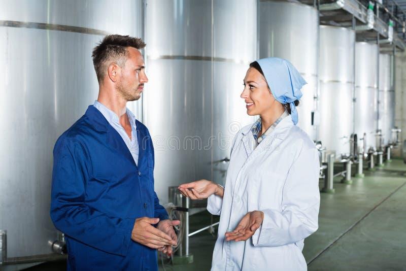 Dois trabalhadores no uniforme protetor que falam na seção secundária da fermentação fotos de stock