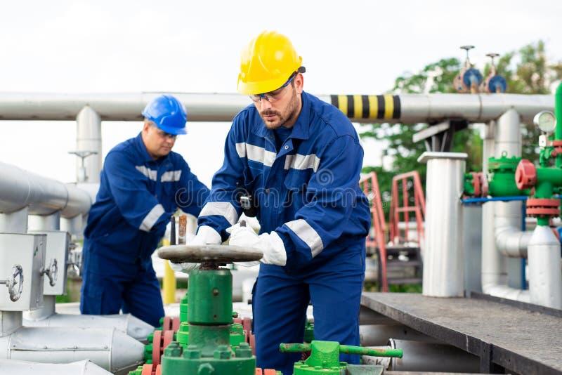 Dois trabalhadores petroquímicas que inspecionam válvulas de pressão em um depósito de gasolina fotografia de stock