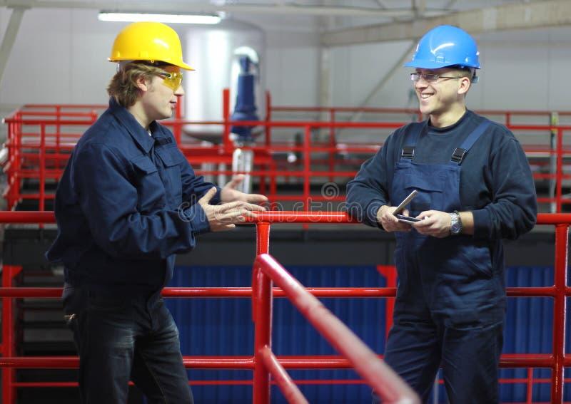 Dois trabalhadores que falam em uma fábrica fotos de stock royalty free