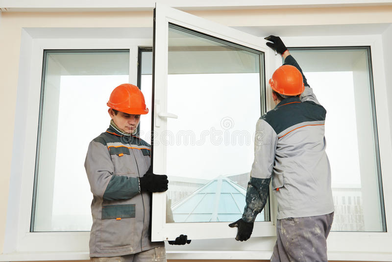 Dois trabalhadores que instalam a janela foto de stock