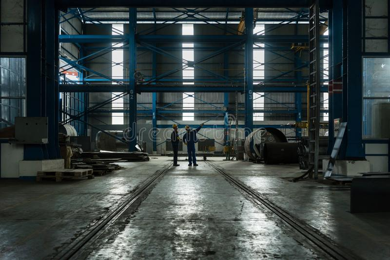 Dois trabalhadores que planeiam o processo de manufatura fotografia de stock