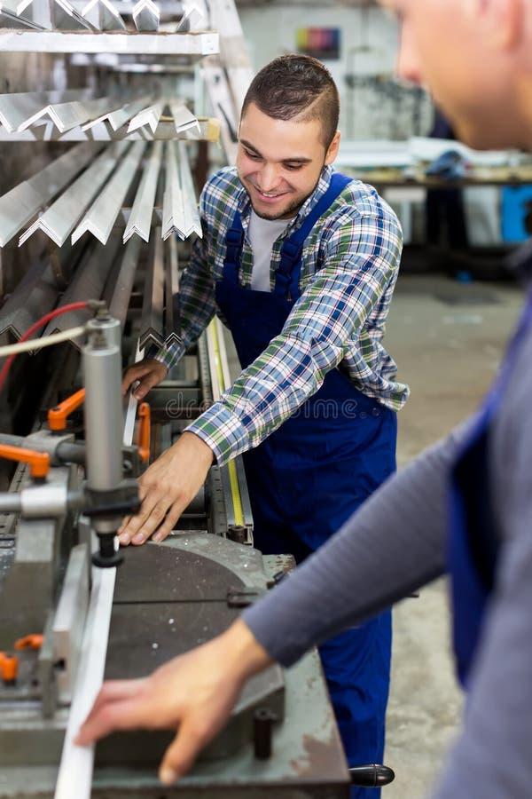 Dois trabalhadores que trabalham em uma máquina imagens de stock