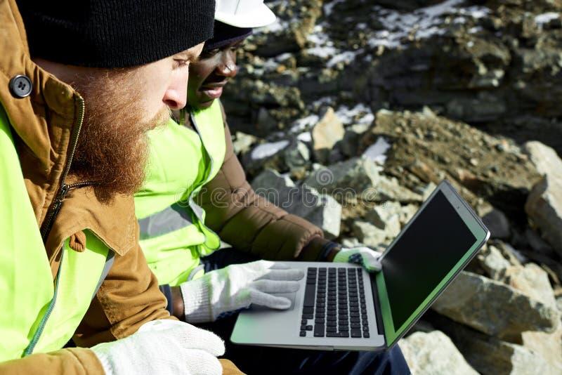 Dois trabalhadores que usam o portátil no local da escavação fotografia de stock