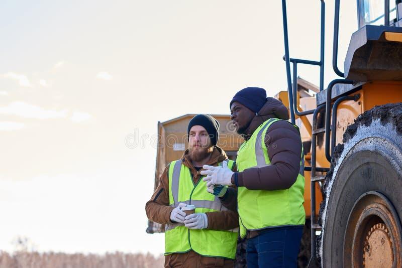 Dois trabalhadores resistentes no local industrial fora imagens de stock